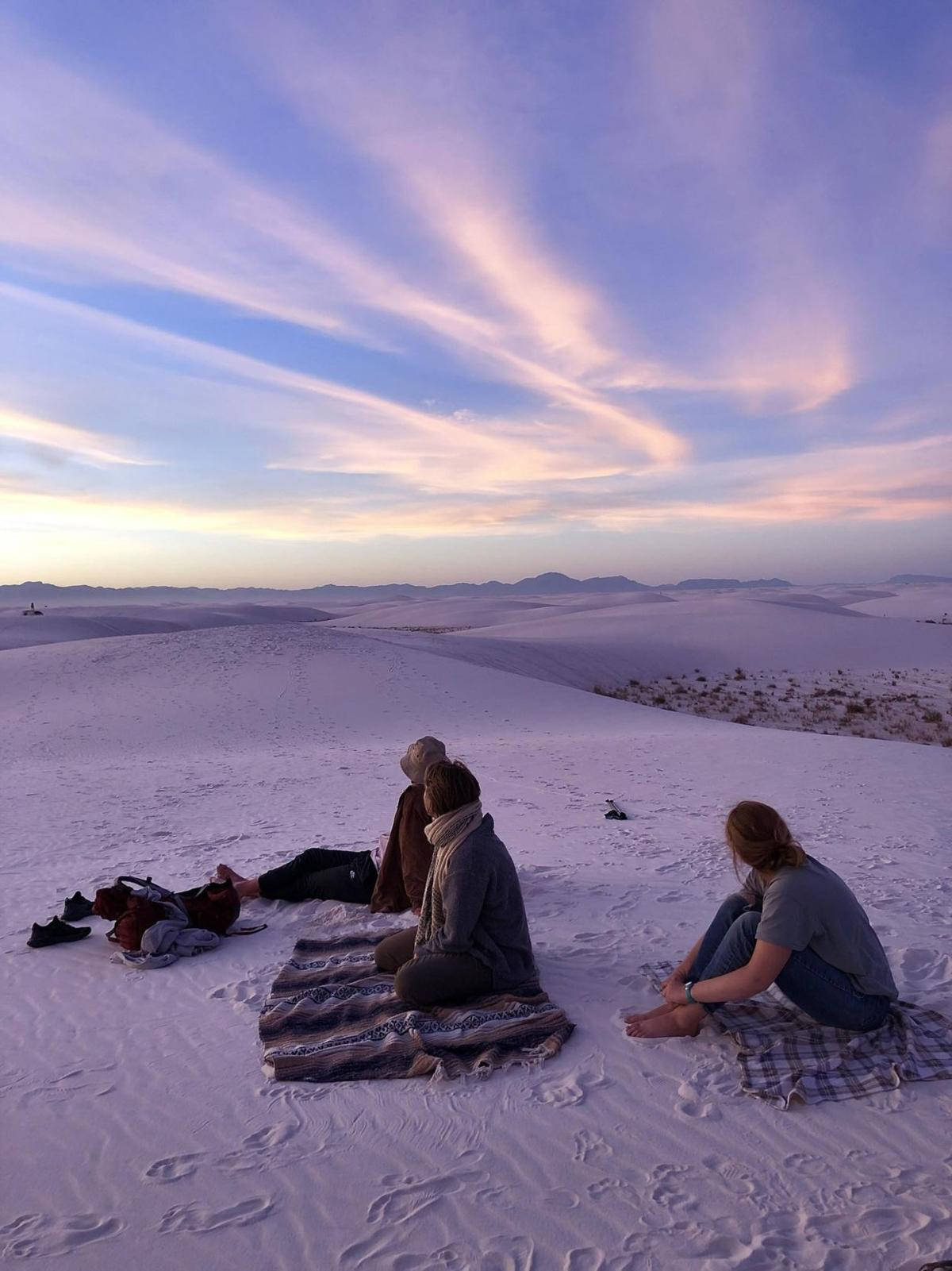 Campers catch the sunset on top of the dunes.