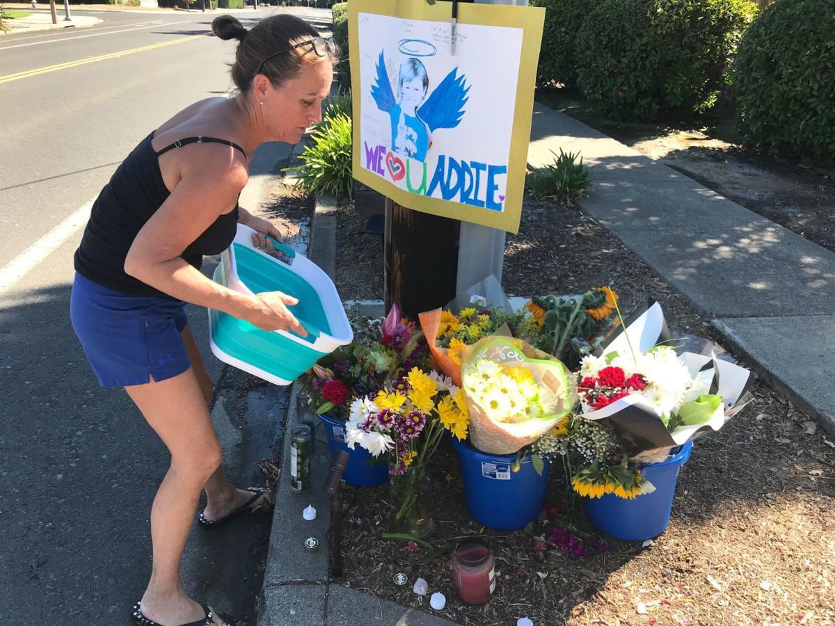 Neighbor Margie Vigil waters flowers left by Addie Dominici's home in Browns Valley