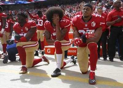 The San Francisco 49's Eli Harold (58), Colin Kaepernick (7) and Eric Reid (35) kneel during the national anthem before a game against the Dallas Cowboys on October 2, 2016, at Levi's Stadium in Santa Clara, Calif.