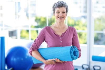 Portrait of mature woman with yoga mat
