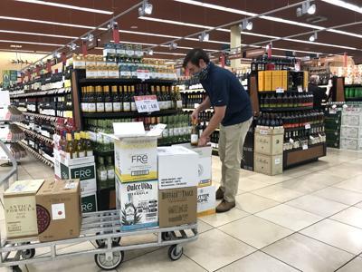 Man stocking wine at Napa's Raley's supermarket wearing face mask