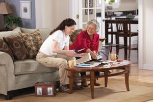 Young woman helping elderly woman cut coupons