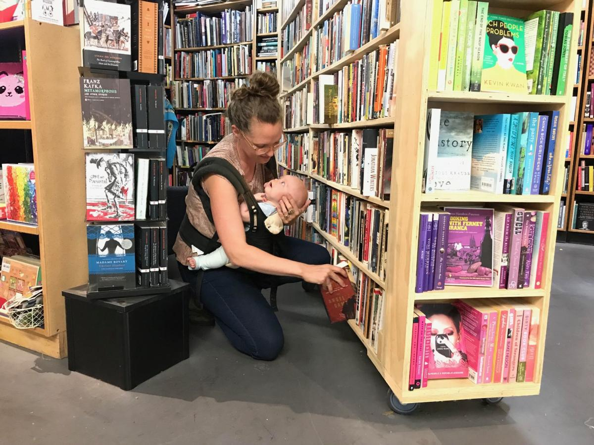Naomi Chamblin shelves books at her store, Napa Bookmine, while holding her new baby Gweneth. The store's rent recently increased 70 percent and Chamblin has asked the community to help support the business.
