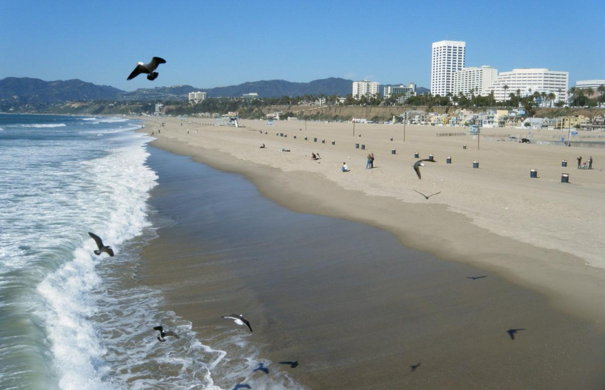 Even on a cool February afternoon, the beach in Santa Monica, CA, attracts a few sun-seekers in this file photo. Santa Monica has become more posh in recent years, leading to price increases at hotels in town.