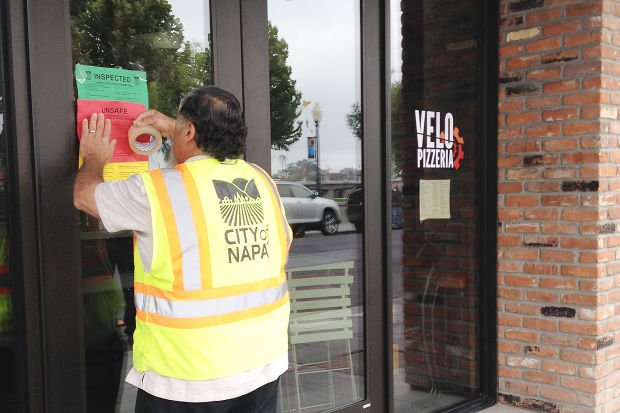 A city employee taping up an unsafe sign on a building after the Napa earthquake