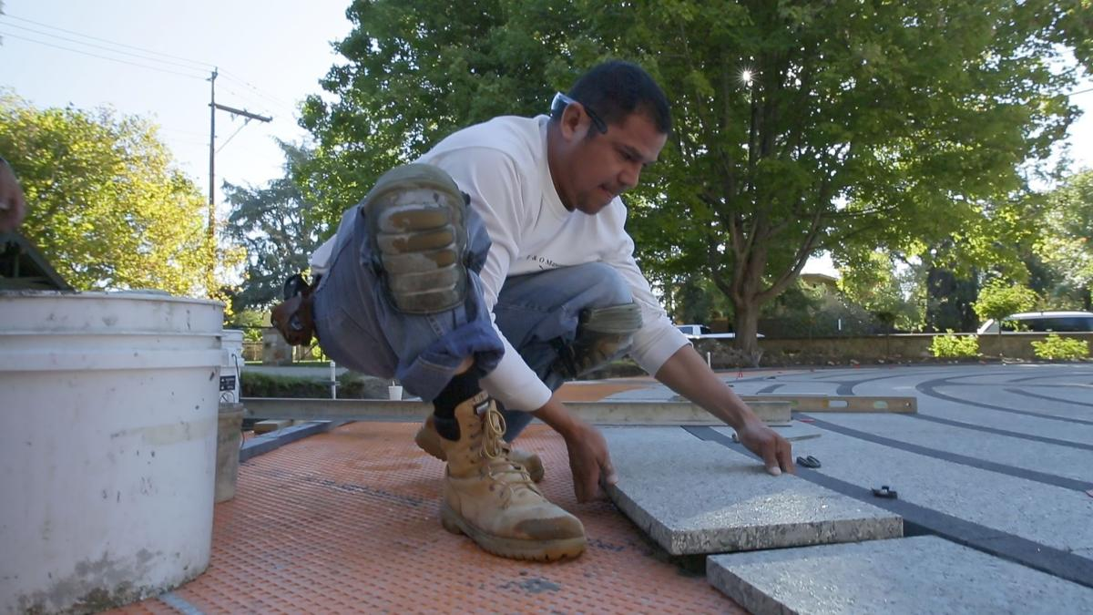 Worker lays a stone