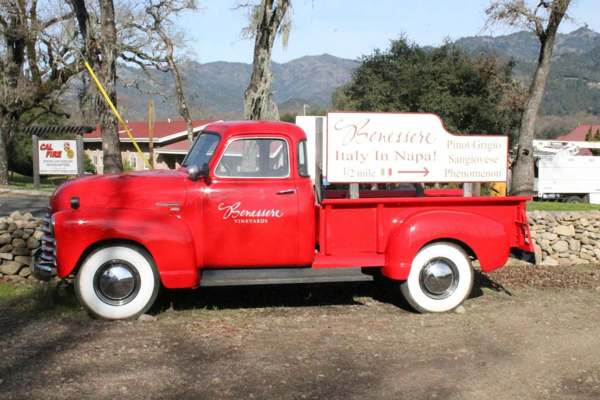 A bright red Chevy truck points the way to Benessere Vineyards