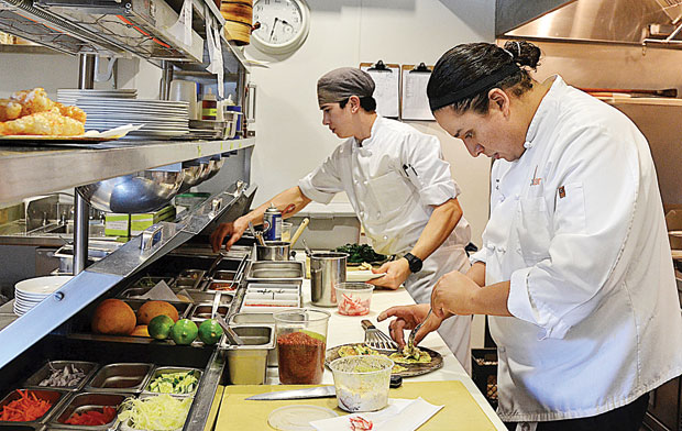 sous chef gustavo rios right assembles dungeness crab salads on scallion pancakes he has just browned in back line cook roland abanico