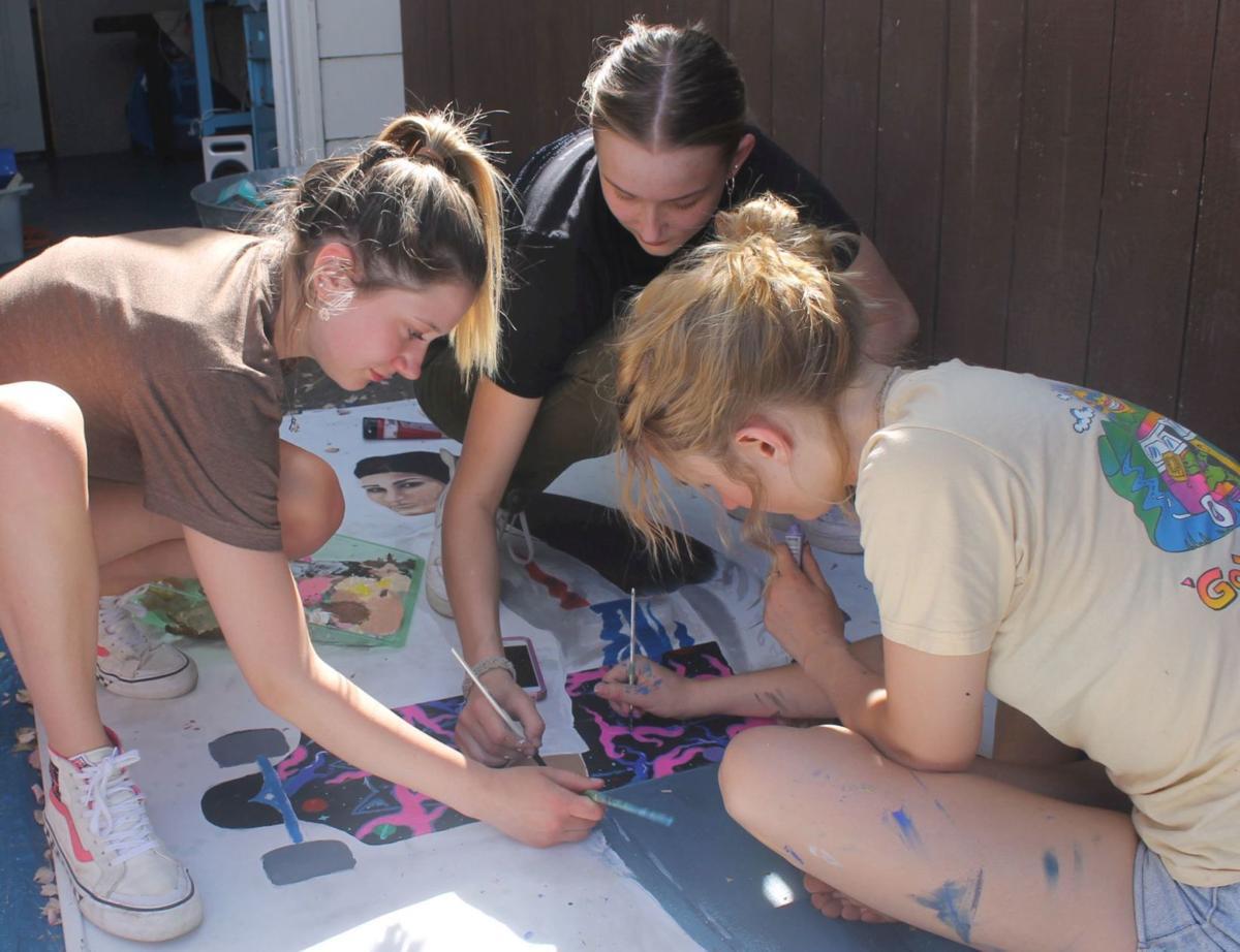 Teens work on Emma Fife's mural