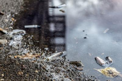 cigarette butts and leaves in autumn puddle