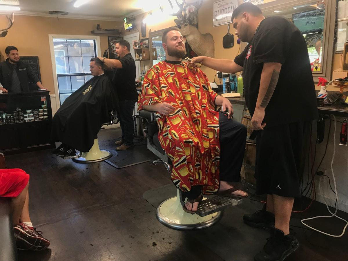 John Lundy (center) getting his hair cut by Shawn Manriquez (right) at Stags Barbershop in Napa.