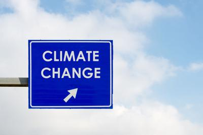 Climate Change words displayed on blue road sign