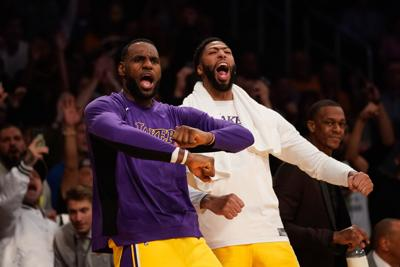 The Los Angeles Lakers' LeBron James, left, and Anthony Davis celebrate on the bench during an October 2019 game against the Memphis Grizzlies at Staples Center in Los Angeles.