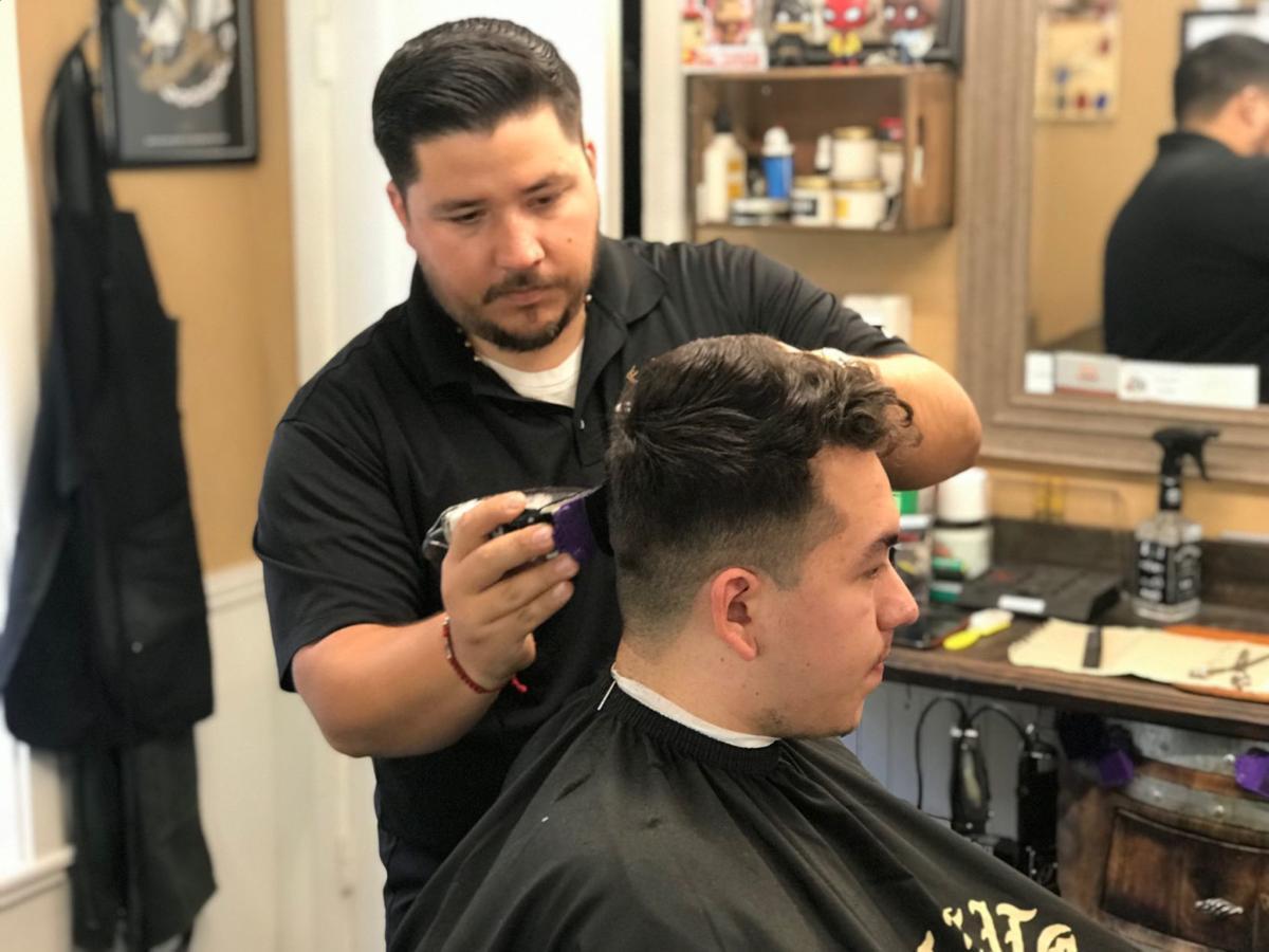 Mario Gonzalez gets his hair cut by Gustavo Peña at Stags Barbershop in Napa.