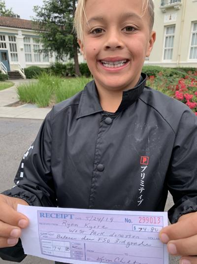 Ryan Kyote with his receipt after paying off the outstanding food service bill for his class at West Park Elementary School.