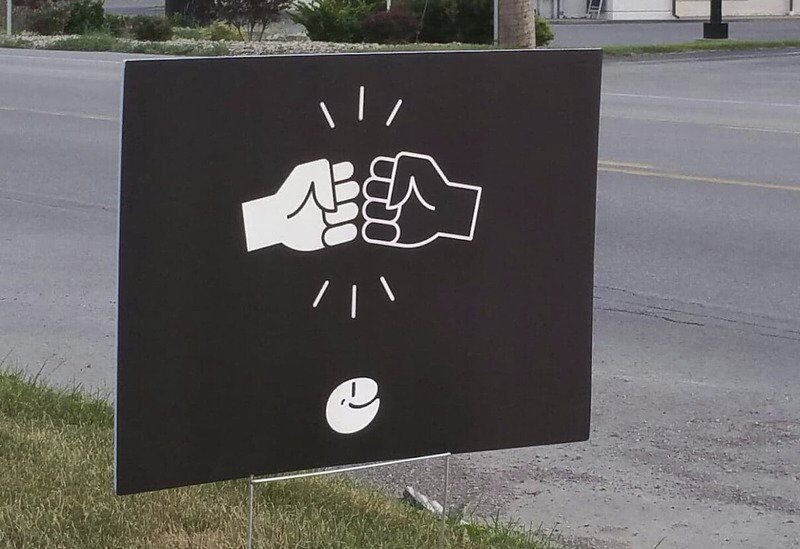 Fist-bump signs aim to promote unity