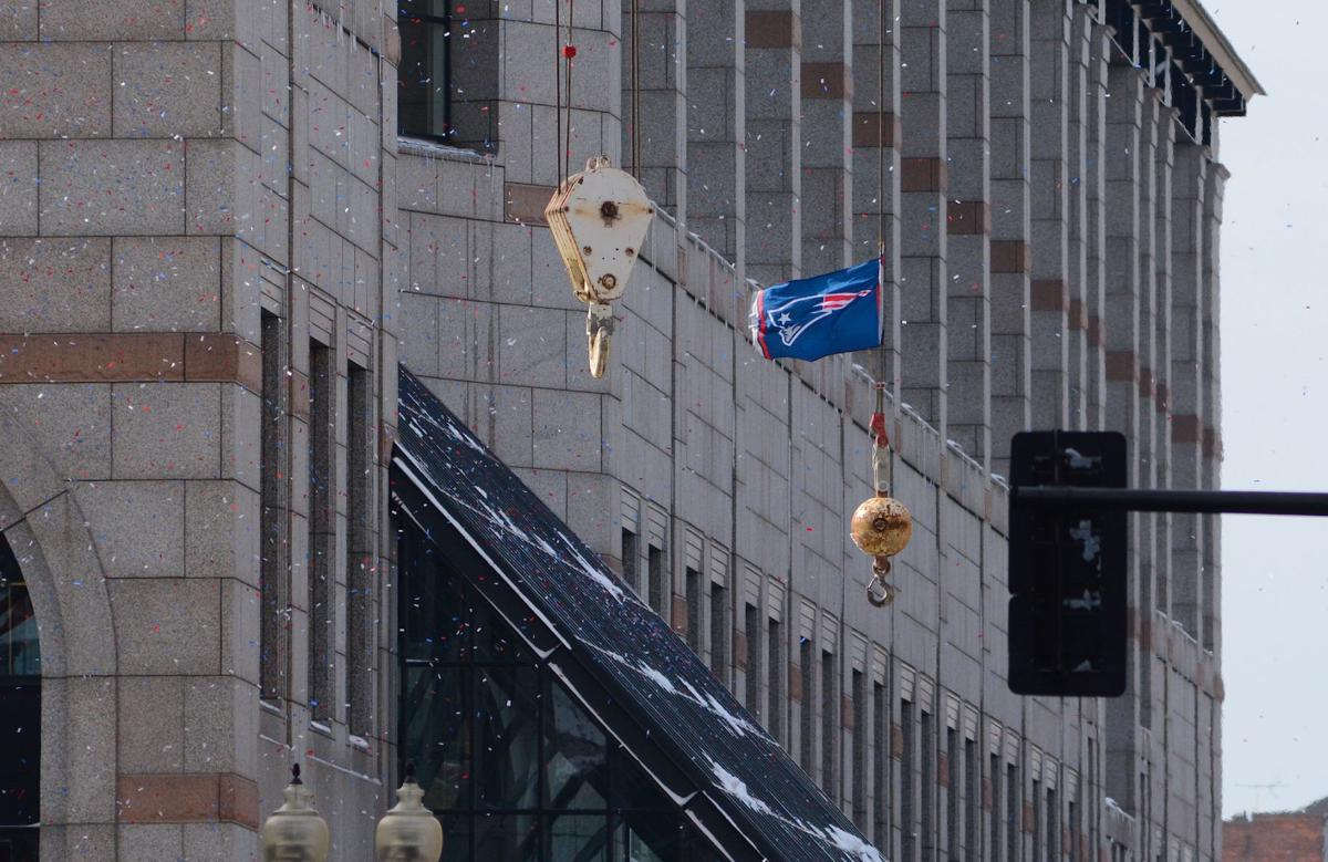 As a confetti cannon launches red, white and blue paper into the air above Boylston Street, construction crews working on the Prudential Center hoist a New England Patriots flag above the street as the parade to celebrate the team's Super Bowl win begins.