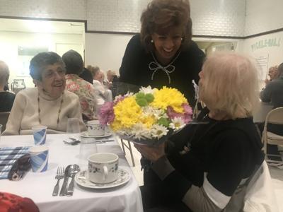 Kaye Shaler receives a bouquet from Senior Center Events Coordinator Carmela Cooke
