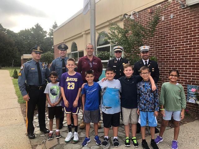 Heroes stand with students of Angelo L. Tomaso school