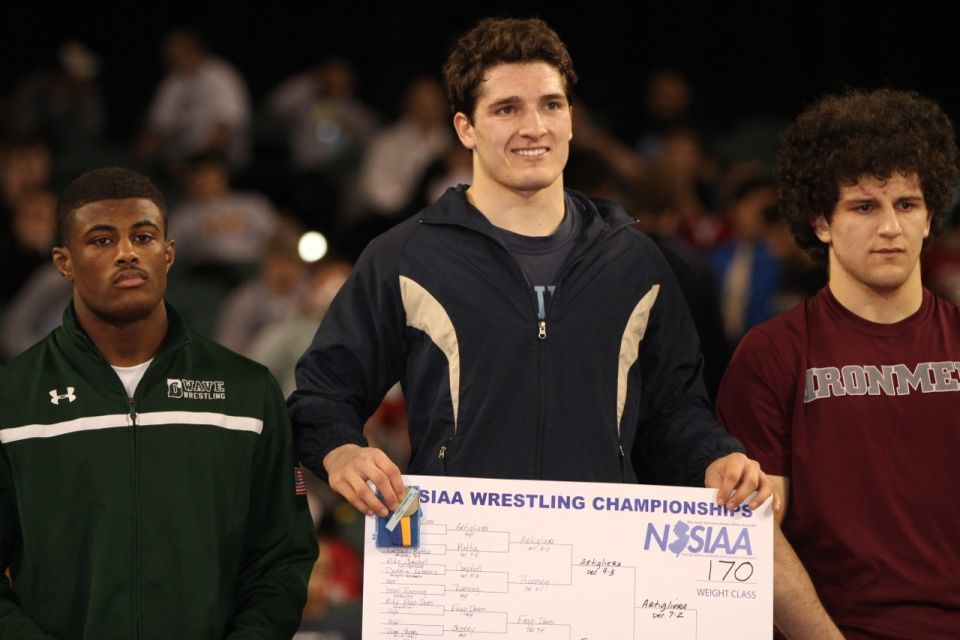 Dillon Artigliere of Roxbury High School, center, holds the 170-pound bracket chart Sunday after winning his second straight state wrestling championship. Photo by Lisa Fassett