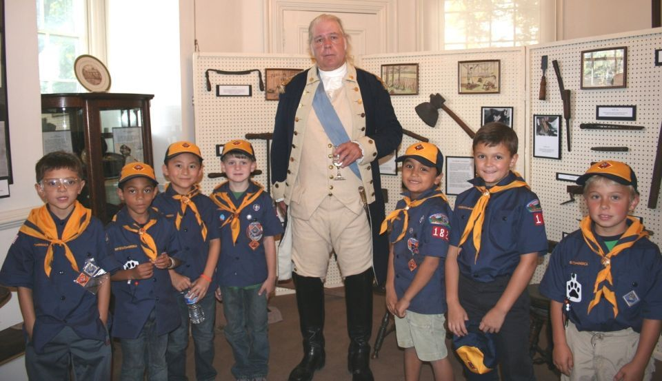 Cub Scouts stand side-by-side the father of our country.