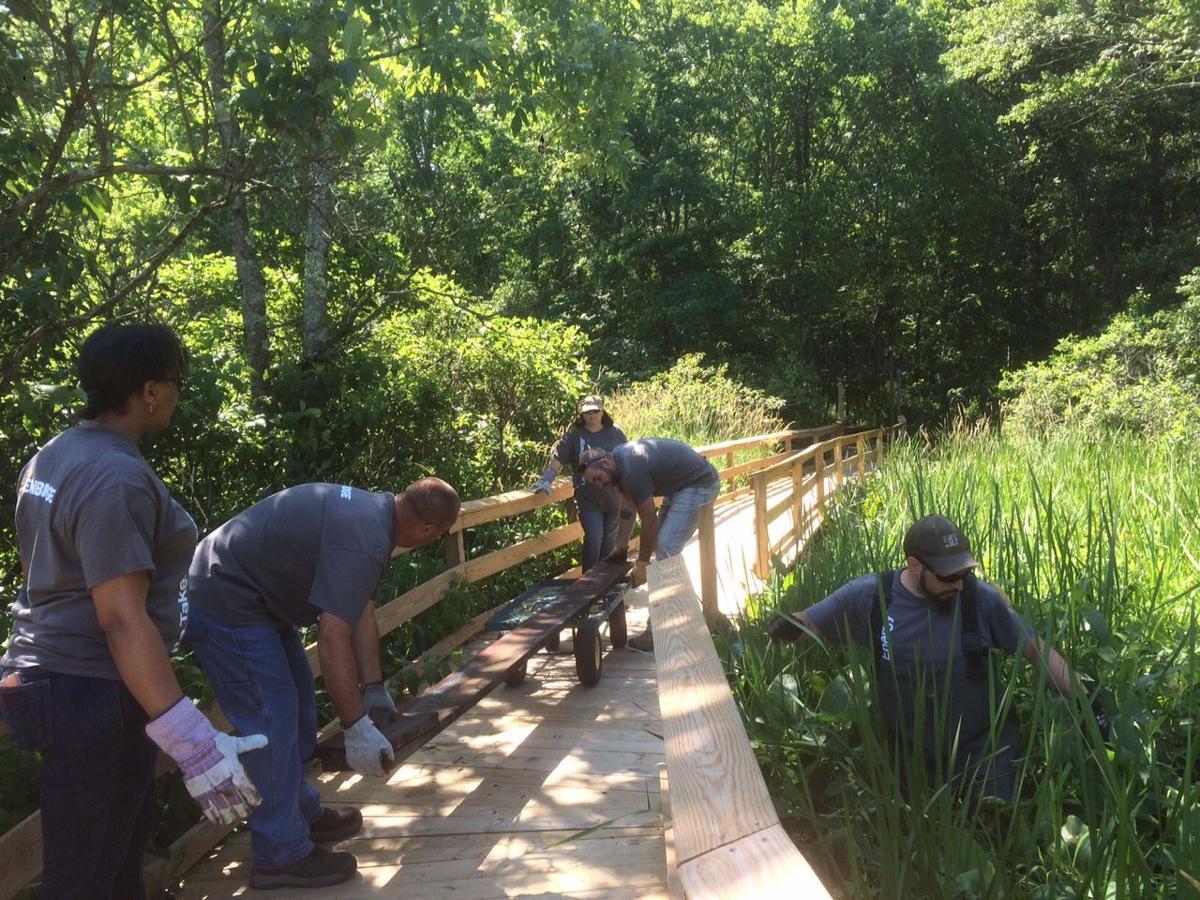 Enbridge voluteers work on EEC Boardwalk