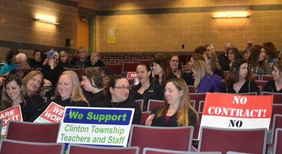 Clinton Township teachers march outside board meeting for contact negotiations.