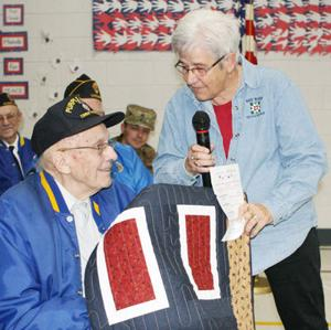 <p>Members of the Hay River Quilters made and donated many quilts to area soldiers returning from the Middle East several years ago. The members decided to continue the tradition by presenting quilts to selected veterans at area Veterans Day ceremonies. On Friday, Nov. 10, at Ridgeland-Dallas Elementary School, quilt guild member Kaye Leaman presents a quilt to Barron resident Jim Anderson, a World War II veteran. Photo by Bob Zientara</p>