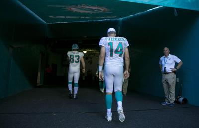 Miami Dolphins quarterback Ryan Fitzpatrick (14) returns to the locker room after a 59-10 loss against the Baltimore Ravens on September 8, 2019, in Miami.