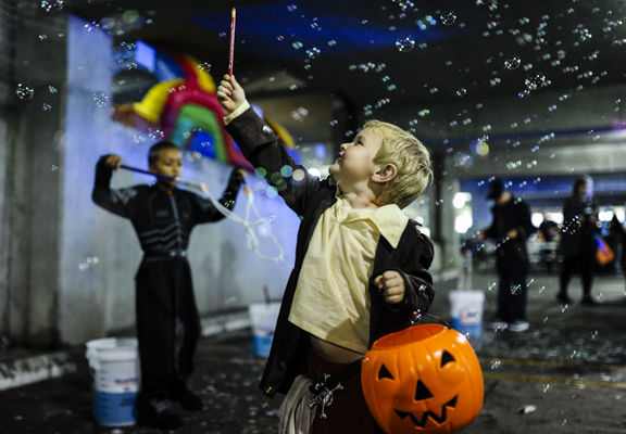 garrett schneider 4 new albany pulls a pencil from his trick or treat bag to pop bubbles while waiting in line for the annual trunk or treat in downtown - Halloween Indiana