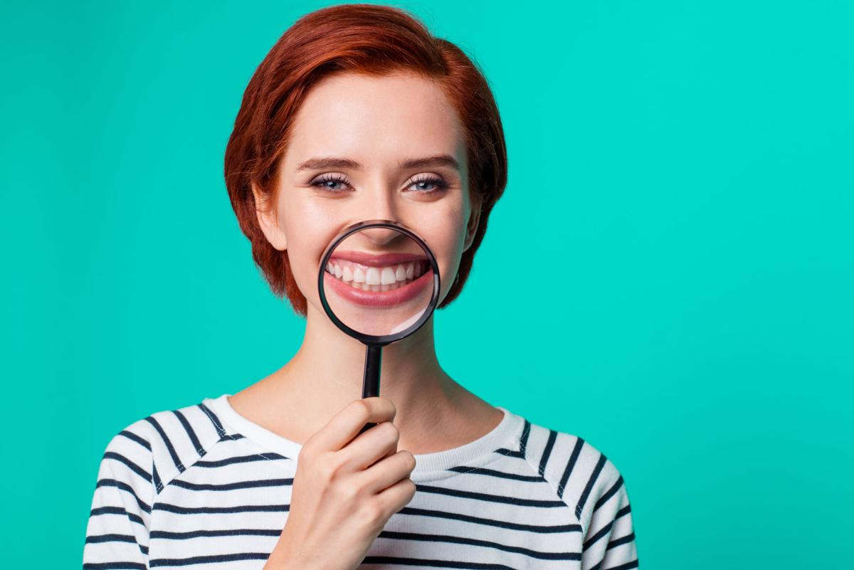 Closeup studio photo portrait of charming satisfied cute friendly caucasian teen girl holding transparent magnifier make wide hollywood smile wearing black pullover isolated bright background