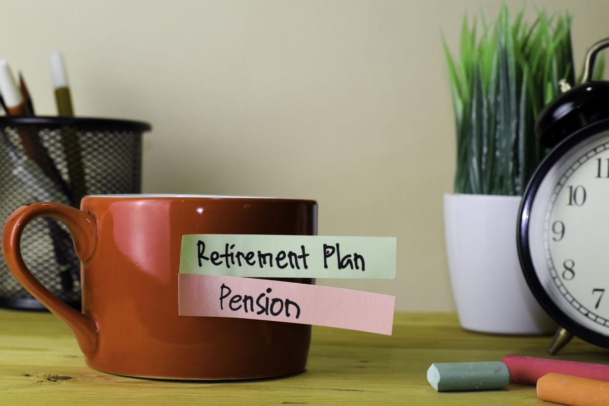 Retirement Plan and Pension. Handwriting on sticky notes in clothes pegs on wooden office desk