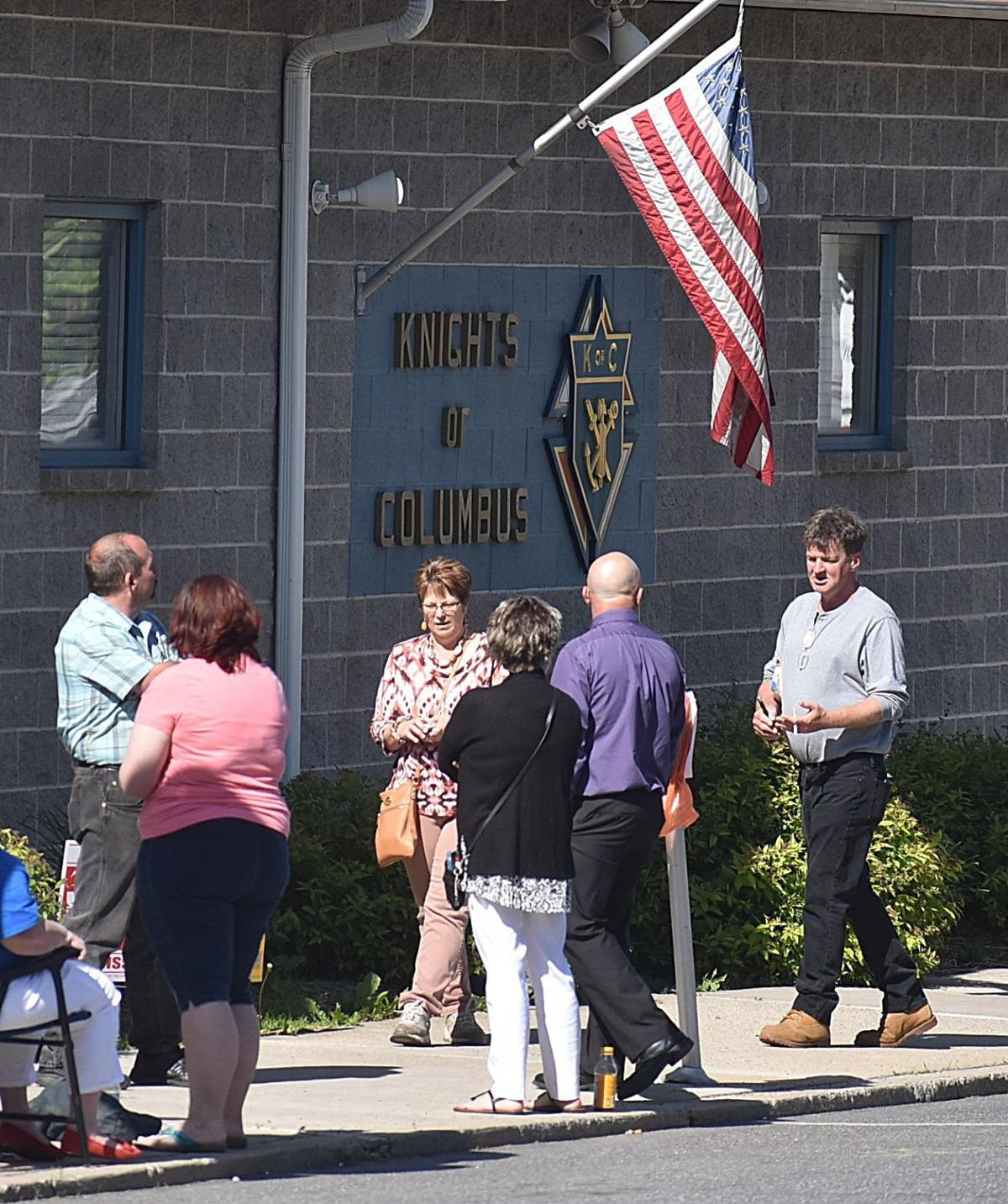 Candidates and volunteers stand outside the 1st Ward polling station