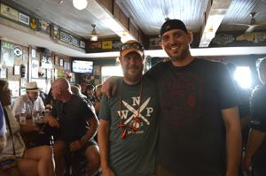 <p>Matt Fox (left) and Dean James (right) take a moment in the middle of the celebration of the opening of the Wooden Nickel Pub's new location – just two doors down from their original place – on Thursday, July 5.</p>