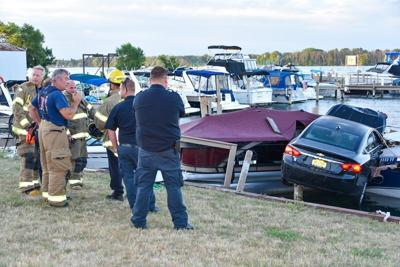Driver says spider caused crash that sent car into boats