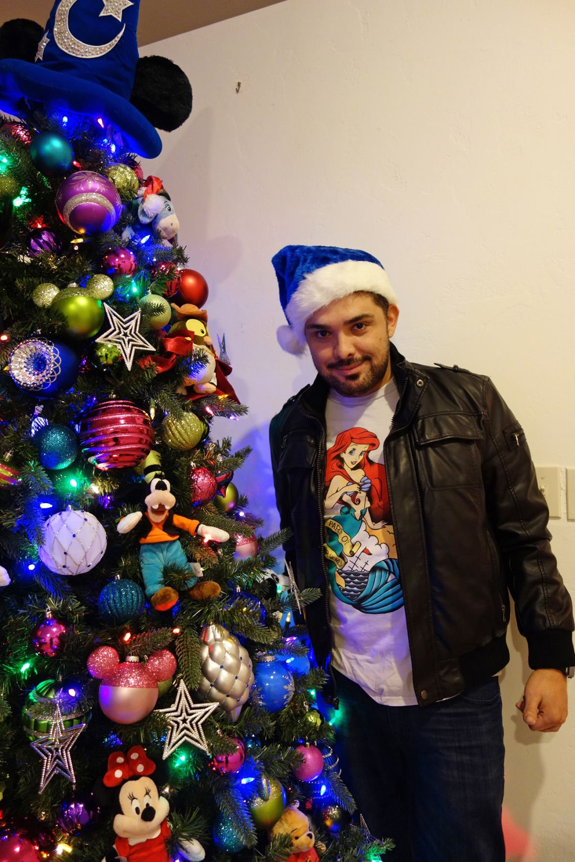 armando guerrero stands next to his disney themed christmas tree