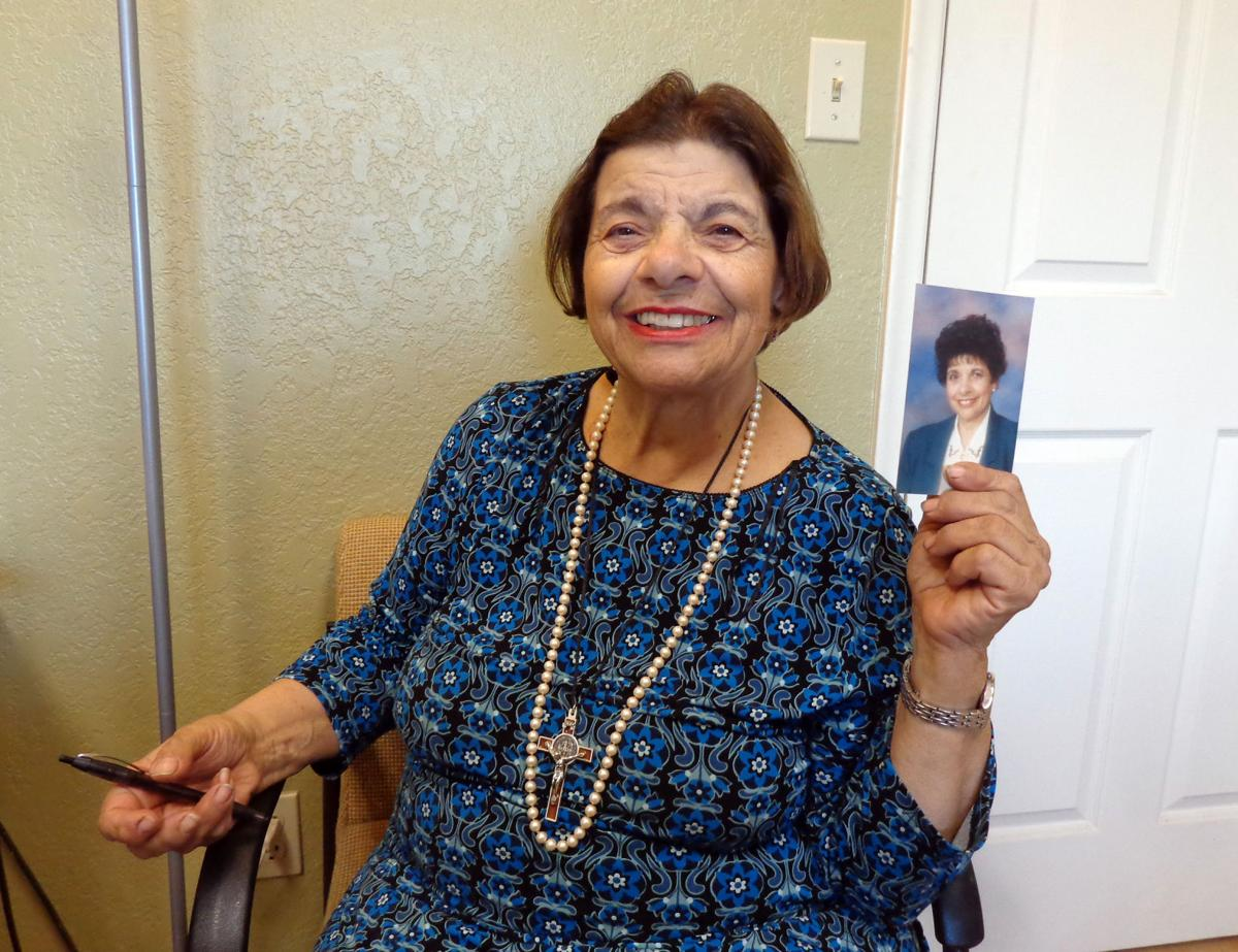 Ann Marie Karam holds up a photo of herself taken during her days as a  teacher. She and her family can trace their roots back to Lebanon.