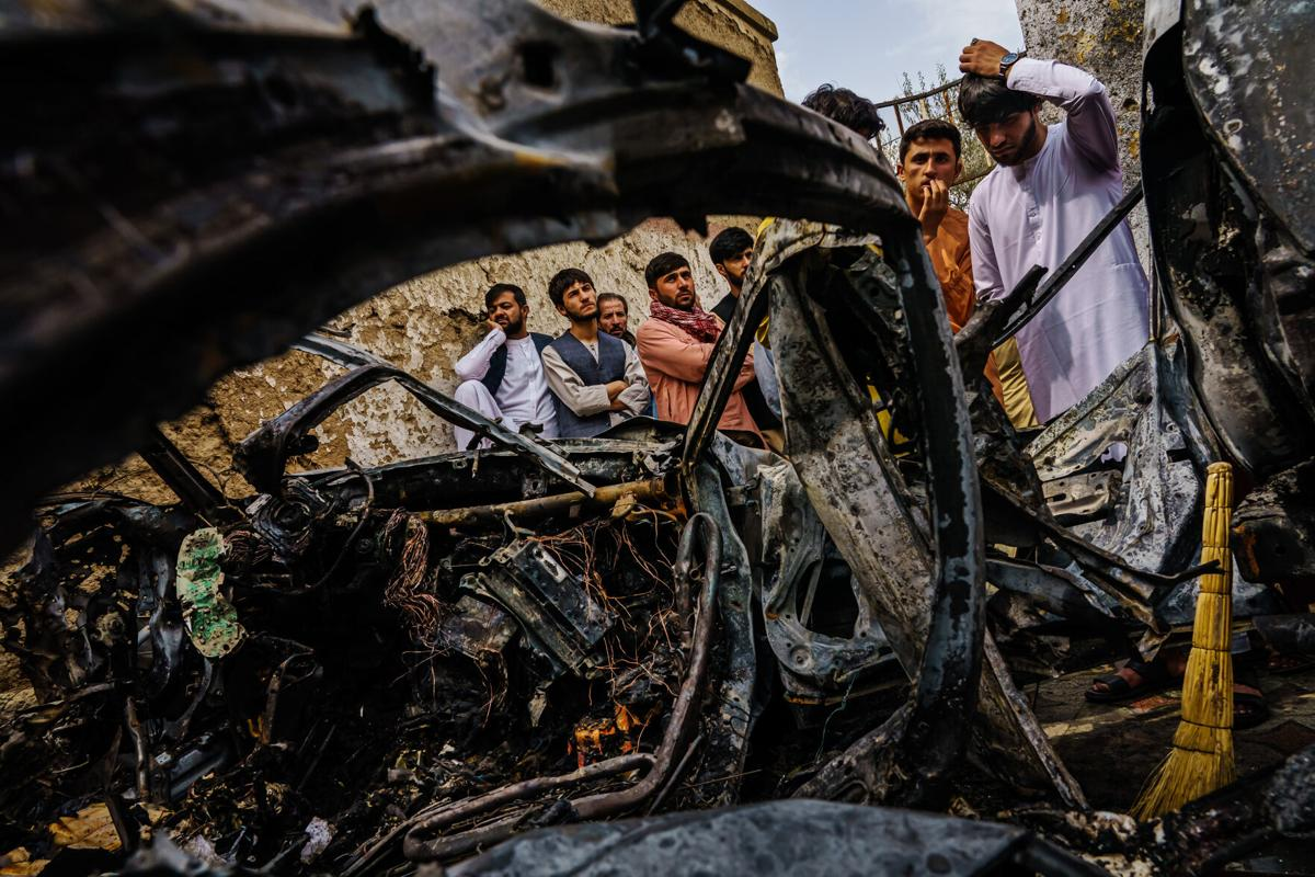Relatives and neighbors of the Ahmadi family gathered around the incinerated husk of a vehicle that the family says was hit by a U.S. drone strike, in Kabul, Afghanistan, Monday, Aug. 30, 2021.