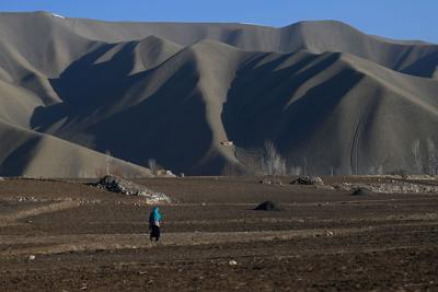 A Hazara woman walks on a land at Dare-Folladi on the outskirts of Bamiyan Province on March 9, 2021.