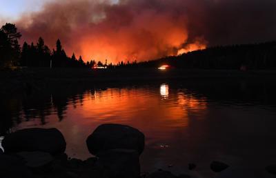 The Caldor fire is reflected off of Caples Lake near the Kirkwood ski resort Wednesday, Sept. 1, 2021, in Lake Tahoe, California.