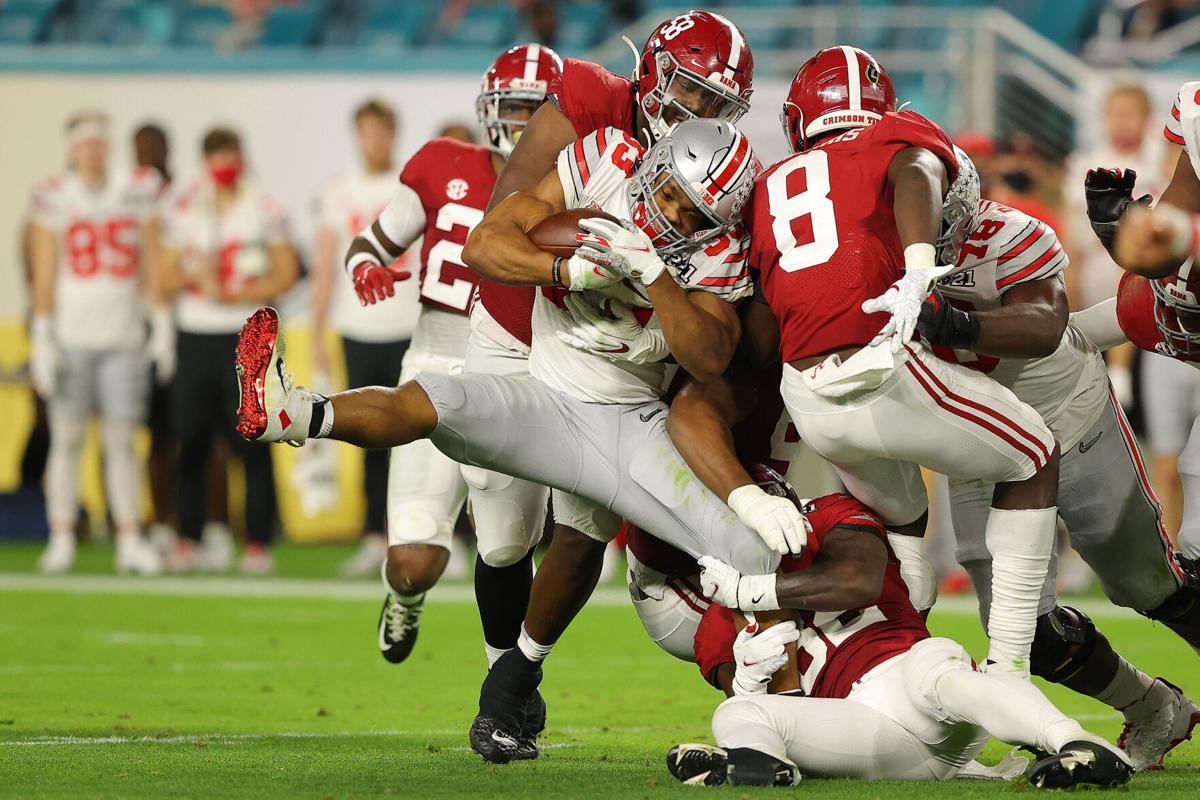 Christian Barmore #58 of the Alabama Crimson Tide tackles Master Teague III #33 of the Ohio State Buckeyes during the second quarter of the College Football Playoff National Championship game at Hard Rock Stadium on Jan. 11, 2021 in Miami Gardens, Florida.