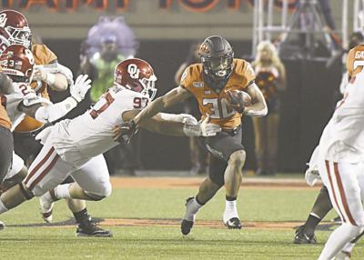 Oklahoma Sooners defensive lineman Marquise Overton (97) tackles Oklahoma State Cowboys running back Chuba Hubbard (30during the game between the Bedlam game between Oklahoma State University and Oklahoma University on November 30,2019 at Boone Pickens Stadium in Stillwater, OK. (june frantz hunt/Transcript)