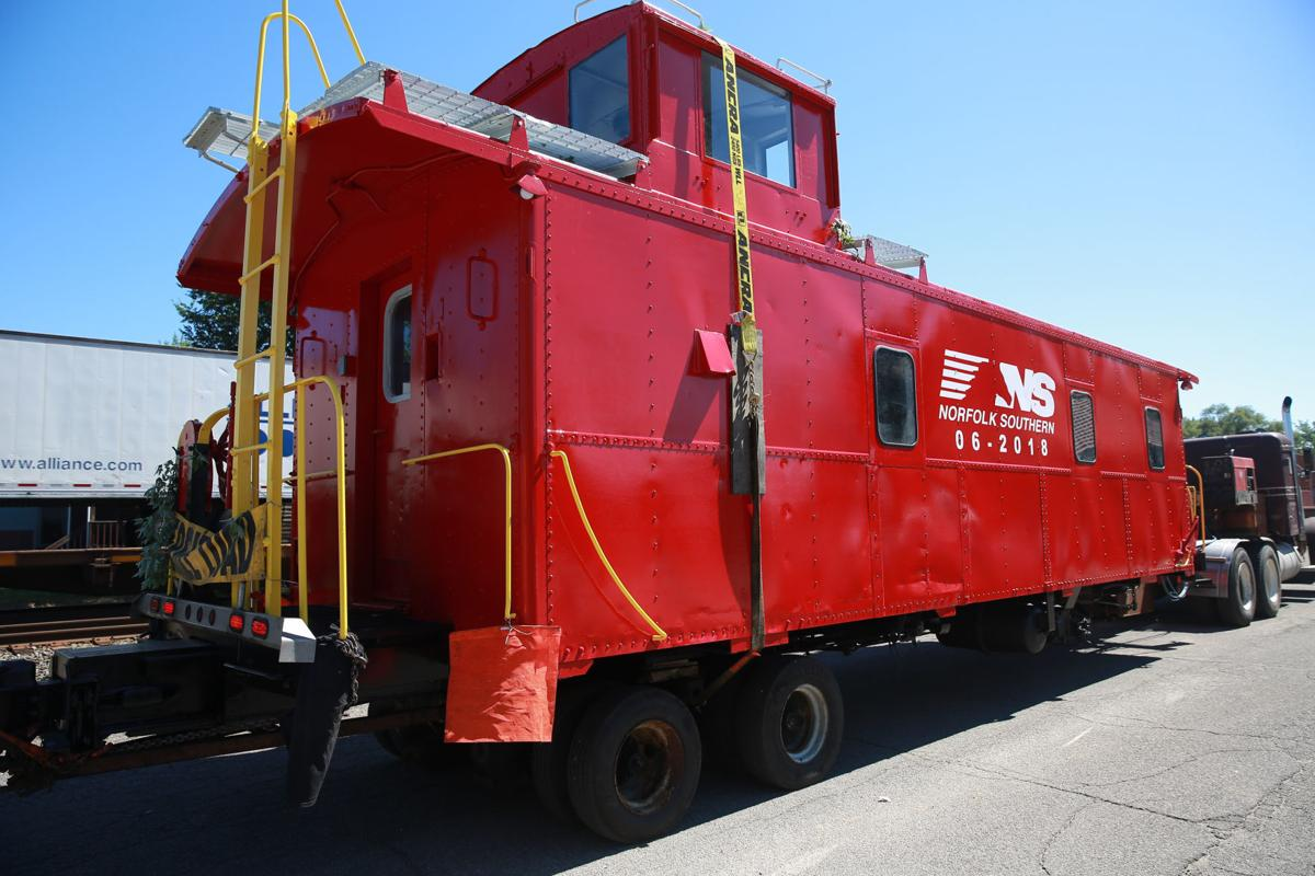 Refurbished caboose, boxcar being placed in downtown