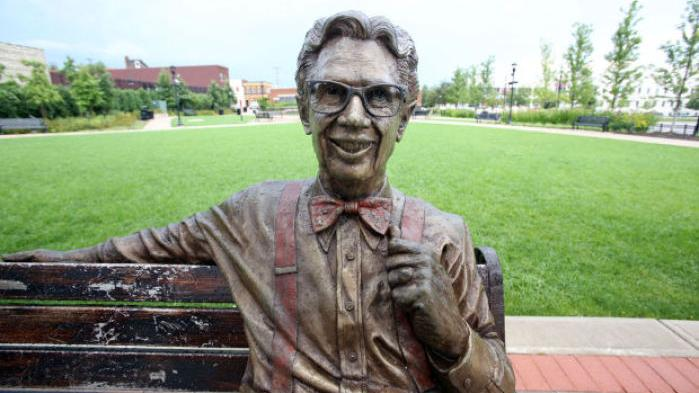 A bronze statue of Orville Redenbacher sitting on a park bench.