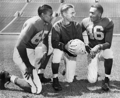 Ex-UCLA Bruins Woody Strode, left, and Kenny Washington, right, listen to Los Angeles Rams coach Adam Walsh in a publicity photo taken at the Memorial Coliseum, published September 7, 1946 in the Los Angeles Times.