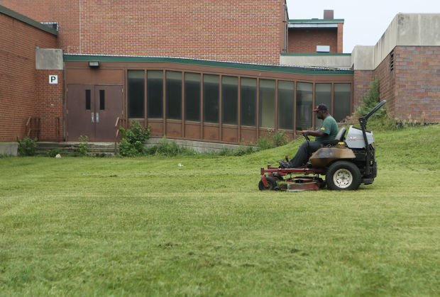 Workers trim grass at Dunbar-Pulaski Middle School in Gary