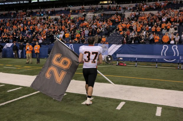 LaPorte's Noah Boardman carries a flag with the old number of his best friend and teammate Jake West
