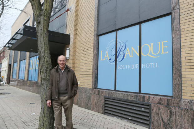 Dr. Claude Gendreau in front of his hotel and restaurant, which was a bank