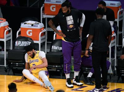 Anthony Davis #3 of the Los Angeles Lakers falls at the Laker bench in the first quarter during game six of the Western Conference first round series at Staples Center on June 03, 2021 in Los Angeles, California.