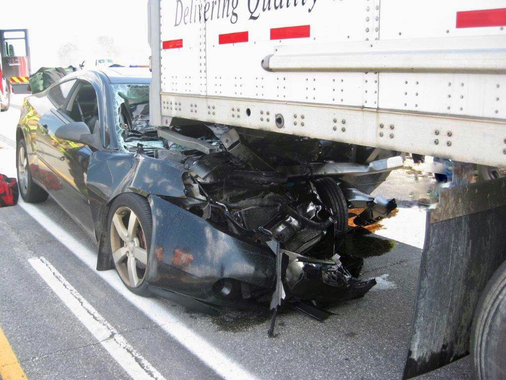 Man trapped inside car after colliding with back of semi, police say